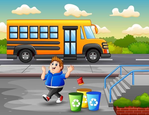 Cena de parque com menino gordo jogando lixo no lixo