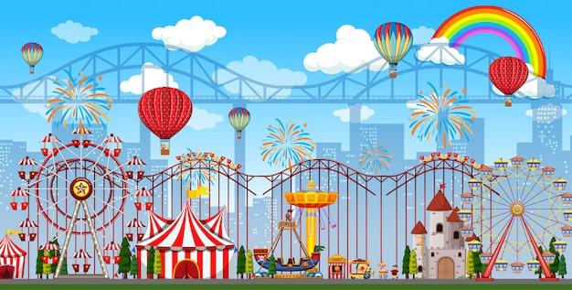 Cena de parque de diversões durante o dia com arco-íris e balões no céu
