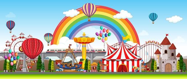 Cena de parque de diversões durante o dia com balões e arco-íris no céu