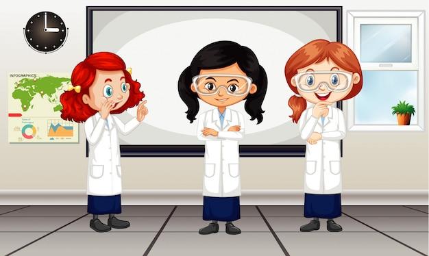 Cena de sala de aula com três meninas em bata de laboratório