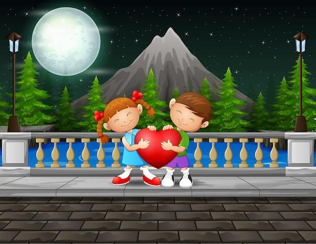 Cena noturna com duas crianças segurando um coração vermelho