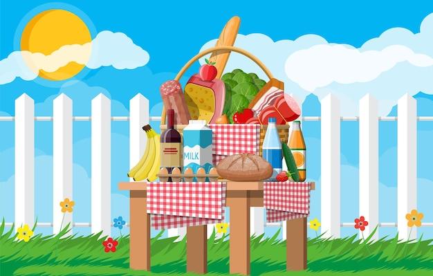 Cesta de piquenique wicker cheia de produtos. vinho, linguiça, bacon e queijo, maçã, tomate, pepino, salada, suco de laranja. grama, flores, céu com nuvens e sol. ilustração vetorial em estilo simples