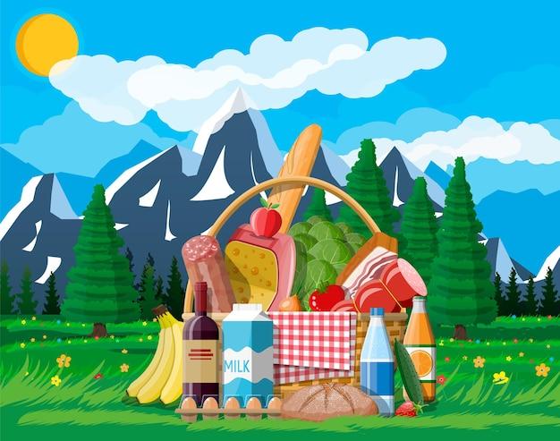 Cesta de piquenique wicker cheia de produtos. vinho, salsicha, bacon e queijo, maçã, tomate, pepino, salada, suco de laranja