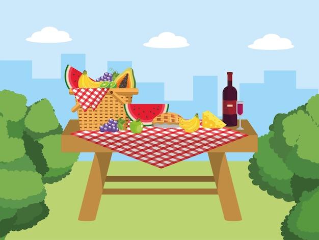Cesta na mesa com comida de vinho e queijo