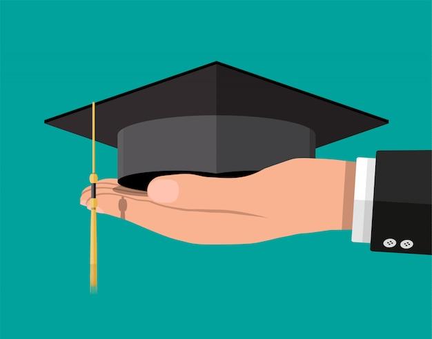 Chapéu de formatura acadêmico na mão. chapéu de estudante