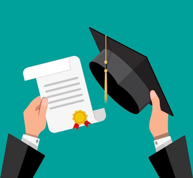 Chapéu de formatura e diploma nas mãos do aluno