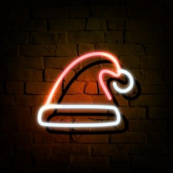 Chapéu de papai noel em néon em uma parede de tijolos escuros