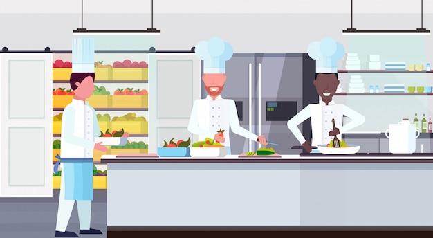 Chef cozinheiro carregando placa com ingredientes da refeição mistura trabalhadores raça cozinhar conceito de trabalho em equipe culinária moderno restaurante comercial cozinha horizontal horizontal