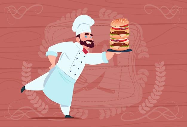 Chef cozinheiro espera grande hambúrguer sorridente chefe de restaurante dos desenhos animados de uniforme branco sobre fundo texturizado de madeira