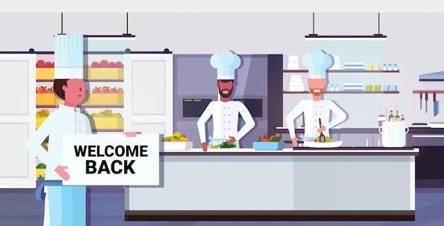 Chef cozinheiro segurando bem-vindo volta placa placa coronavírus quarentena está terminando a vitória sobre o conceito covid-19