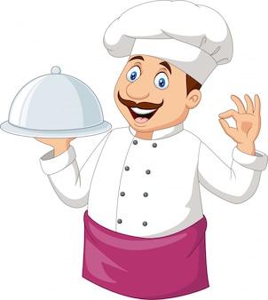 Chef engraçado dos desenhos animados, segurando uma bandeja de prata e sinal de ok