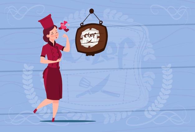 Chef feminino cozinheiro feliz sorrindo chefe dos desenhos animados em uniforme de restaurante sobre o fundo texturizado de madeira