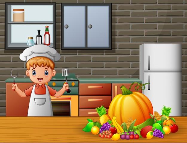 Chef garotinho segurando uma espátula e garfo na cozinha