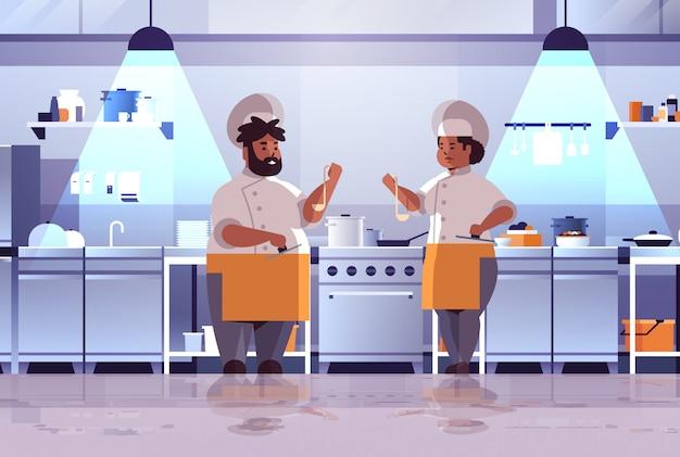 Chefs profissional preparação e degustação pratos mulher afro-americano homem uniforme em pé perto de fogão cozinha conceito comida cozinha interior moderno apartamento comprimento total horizontal