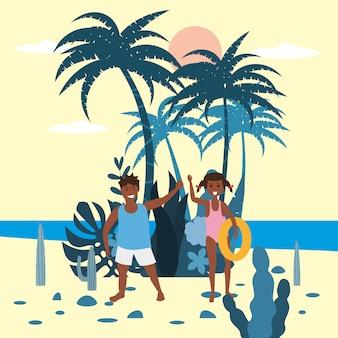 Childs menina e menino com um anel de borracha no fundo de plantas exóticas do mar de palma