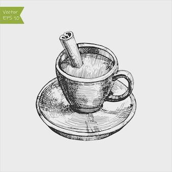 Chocolate quente em uma xícara com bastões de canela