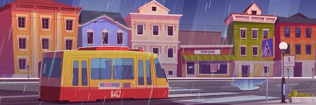 Chuva na rua da cidade com casas, bonde e estrada de carro vazia com faixa de pedestres.
