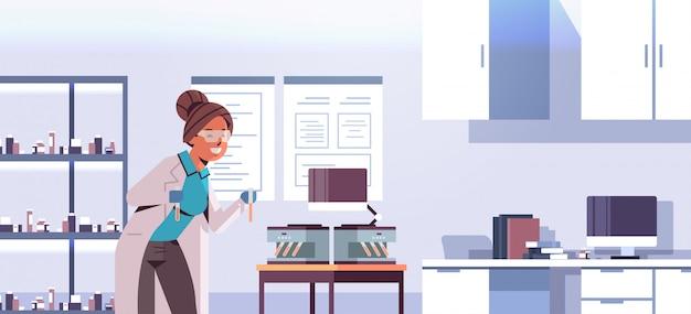 Cientista segurando tubos de ensaio com amostras de sangue, mulher de uniforme, usando a máquina médica analisador