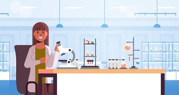 Cientista usando microscópio e tubos de ensaio mulher de uniforme, sentado à mesa