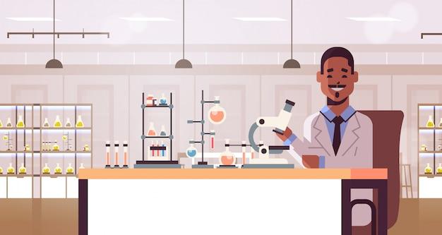 Cientista usando microscópio e tubos de ensaio