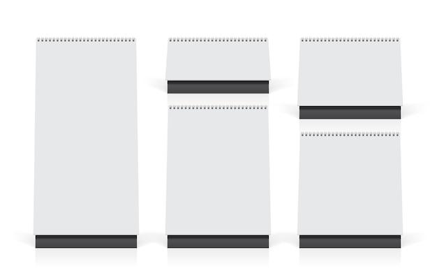 Cinco calendários brancos em cima da mesa