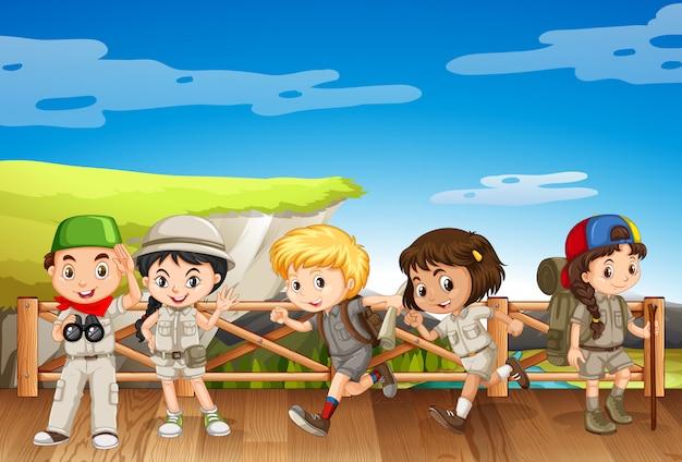 Cinco crianças em traje de safári na ponte