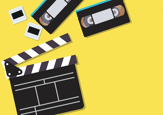 Clapper de filme e fitas cassete de vídeo em fundo amarelo