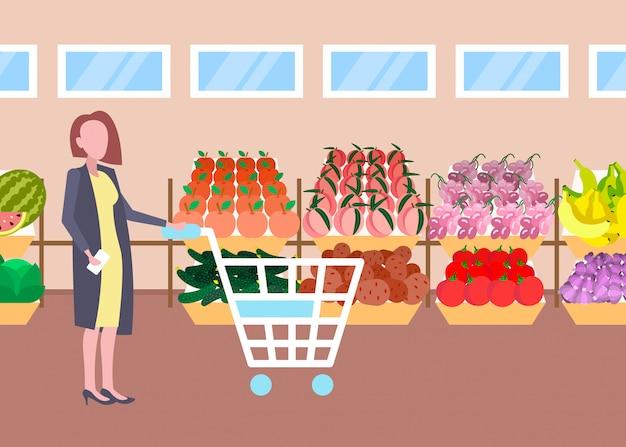 Cliente mulher segurando carrinho carrinho comprando frutas orgânicas frescas legumes moderno supermercado shopping interior personagem de desenho animado feminino comprimento total plana horizontal