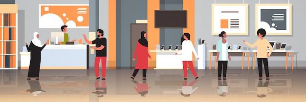 Clientes de corrida de mistura em tecnologia moderna loja interior visitantes escolhendo computador digital laptop tela de tv smartphone aparelhos eletrônicos mercado horizontal horizontal