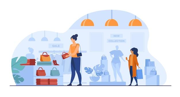 Clientes do sexo feminino às compras na loja de roupas