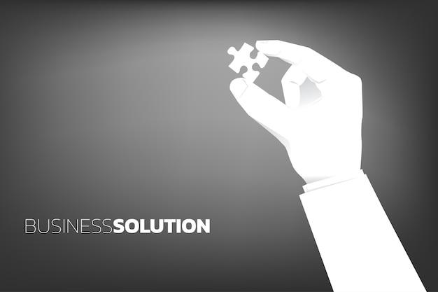 Close-up mão de empresário segurar pedaço de quebra-cabeça no ar