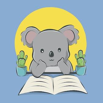 Coala de desenho animado lendo um livro sobre a mesa