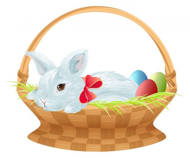 Coelhinho da páscoa na cesta de vime. coelhinha de páscoa sentado na cesta com ovos de cor