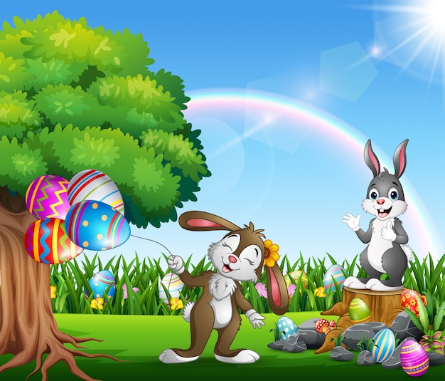 Coelhinhos da páscoa e ovo colorido no jardim