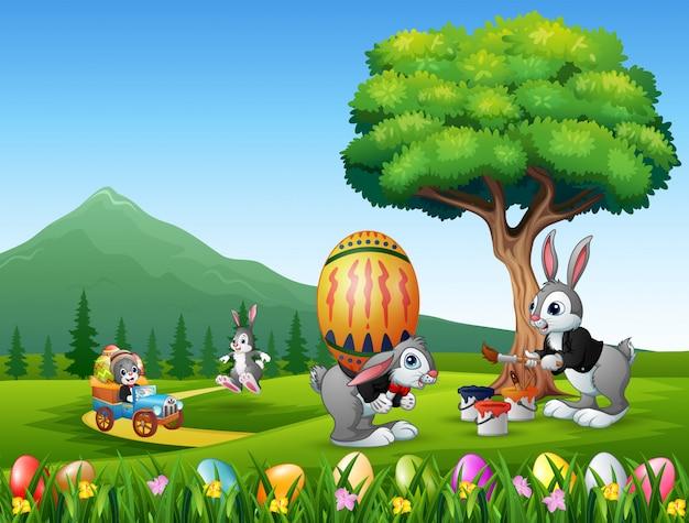 Coelhinhos da páscoa felizes pintando e segurando o ovo