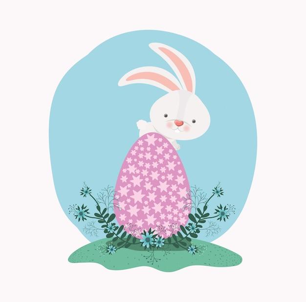Coelho bonito com ovo pintado e flores no jardim