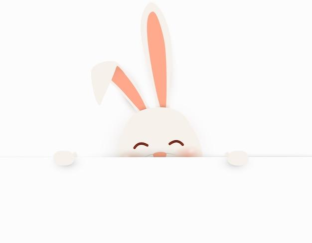 Coelho coelhinho em pé atrás de um cartaz em branco, mostrando um grande cartaz em branco. personagem de coelho bonito e engraçado dos desenhos animados com espaço em branco da cópia.