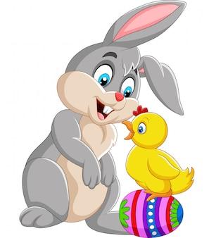 Coelho de desenho animado com um pintinho de pé no ovo de páscoa