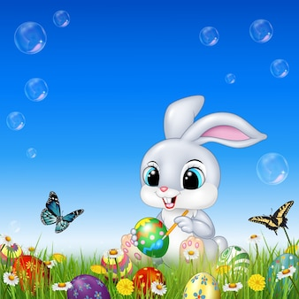 Coelho de desenho animado, decorando um ovo de páscoa