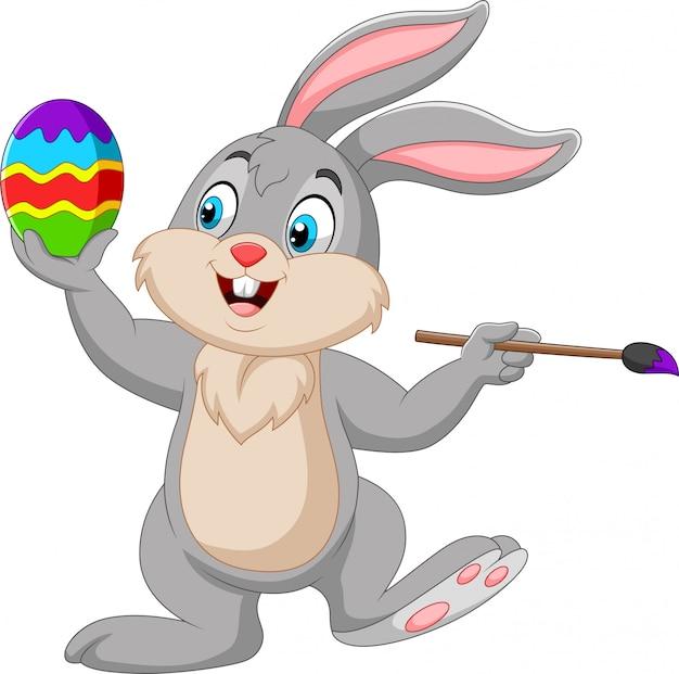 Coelho de desenho animado, pintando um ovo de páscoa