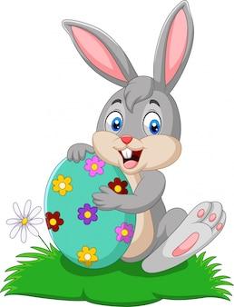 Coelho de desenho animado, segurando o ovo de páscoa
