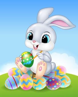 Coelho de páscoa dos desenhos animados, pintando um ovo sobre os ovos de páscoa