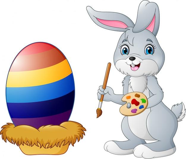 Coelho de páscoa dos desenhos animados, pintando um ovo