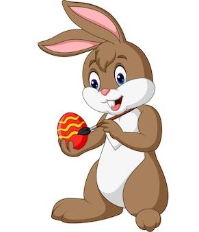 Coelho de páscoa engraçado dos desenhos animados, pintando um ovo