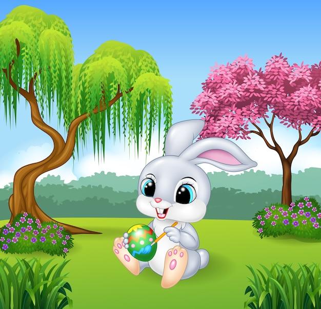 Coelho de páscoa feliz dos desenhos animados, pintando um ovo sobre a rocha