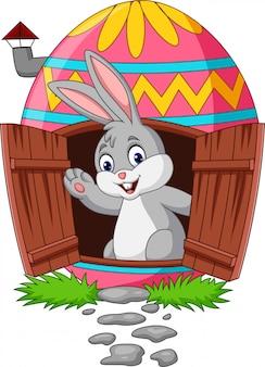 Coelho dos desenhos animados com casa de ovos de páscoa decorados
