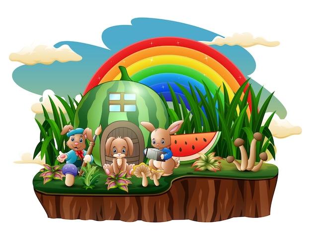 Coelhos felizes brincando em frente à ilustração da casa de melancia