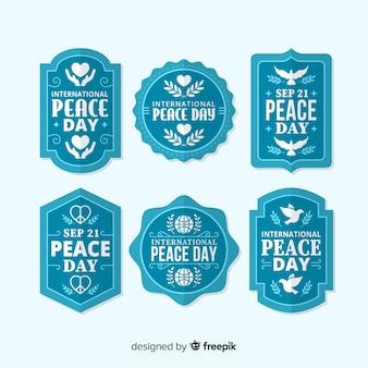 Coleção de crachá azul dia da paz em design plano