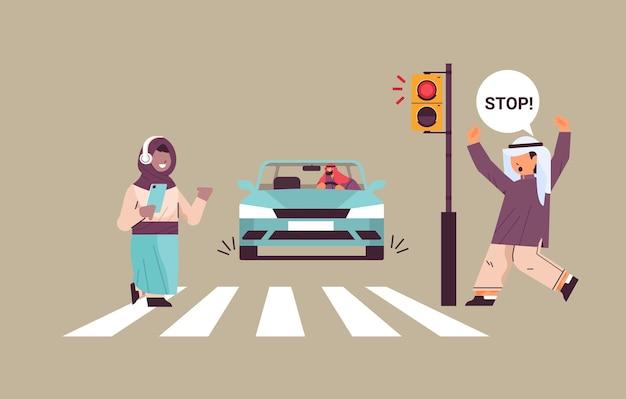 Colegial com smartphone e fones de ouvido cruzando a estrada no semáforo vermelho motorista árabe pára o carro imediatamente segurança rodoviária