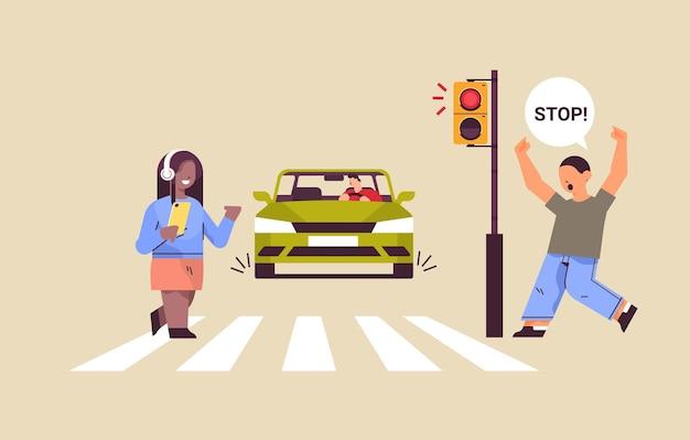 Colegial com smartphone e fones de ouvido cruzando a estrada no semáforo vermelho motorista para o carro imediatamente segurança na estrada